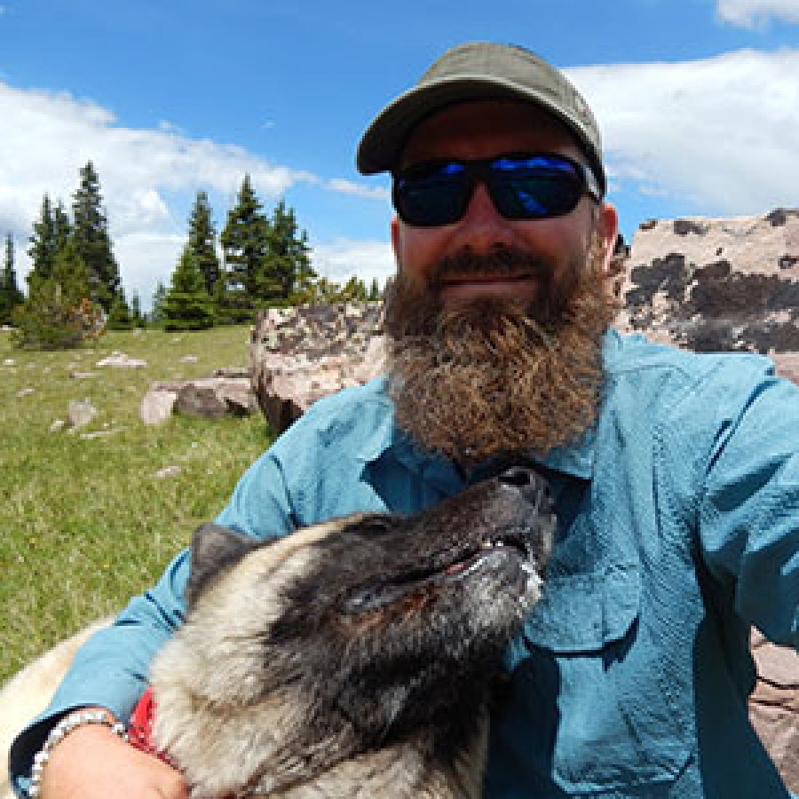Jason with his Akita, Ita Marie, on a monitoring trip in the Uintas.
